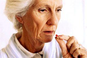 пожилая женщина пьет лекарство
